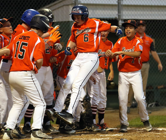 DAVID LE/Staff photo. Beverly's Charlie Mack (6) leaps high in the air as he joyfully arrives at home plate following his two-run homer against Manchester-Essex in the District 15 Championship. 7/14/16.
