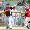 DAVID LE/Staff photo. Danvers National first baseman Nolan Hills stretches at first and snags a throw up the line to retire sprinting Amesbury runner Jake Harring, right. 7/2/16.