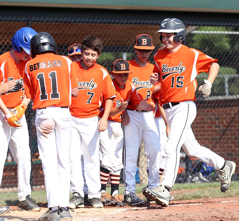 DAVID LE/Staff photo. Beverly's Joey Loreti (15) is greeted at home plate after launching a homer against Fairhaven/Acushnet on Friday afternoon. 7/29/16.