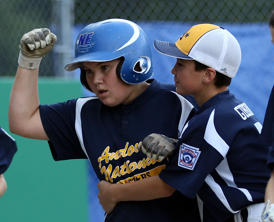 DAVID LE/Staff photo. Andover National first baseman Owen Christopher pumps his fist while getting hugged by teammate Brian Gibson after Christopher launched a grand slam off Beverly relief pitcher Brennan Frost. 7/21/16.