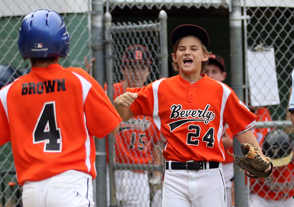 DAVID LE/Staff photo. Beverly's Joe Kotwicki, right, happily greets teammate Joe Brown (4) at home plate after he scored the game tying run. 7/8/16.