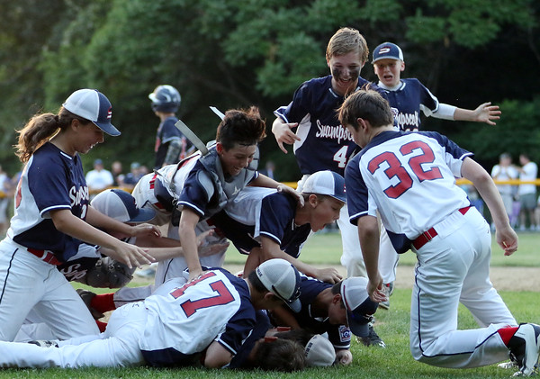 DAVID LE/Staff photo. The Swampscott Big Blue little league team pig piles on top of closer Mathew Schroeder after he got a groundout to second base to retire Peabody West and clinch a 10-7 win in the District 16 Championship on Friday evening. 7/15/16.