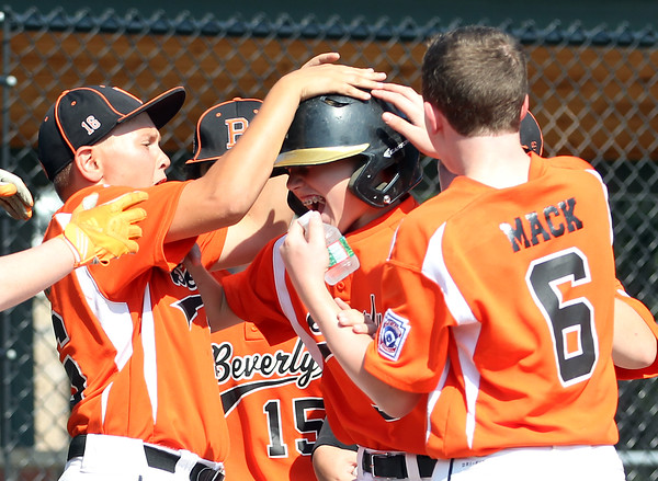 DAVID LE/Staff photo. Beverly's Griffin McCay, center, gets mobbed by his teammates after hitting a homer against Fairhaven/Acushnet. 7/29/16.