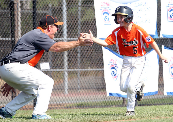 DAVID LE/Staff photo. Beverly's Griffin McCay (5) flahses a wide smile while getting a high five from manager Brady Frost following McCay's homer. 7/29/16.
