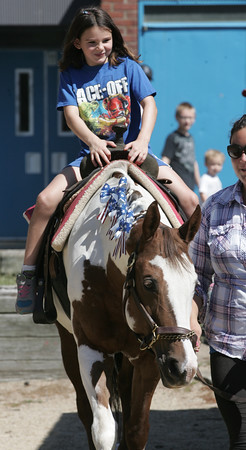KEN YUSZKUS/Staff photo.  Makayle Downing, 7, has a pony ride at the Peabody July 4 activities held at the O'Connor Park at the Welch School.   07/04/16.
