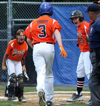 DAVID LE/Staff photo. Beverly's Austin Bernard, left, and Nick Fox, right, scream in excitement as they greet teammate Brennan Frost at home plate following a solo homer to put Beverly up 1-0. 7/14/16.