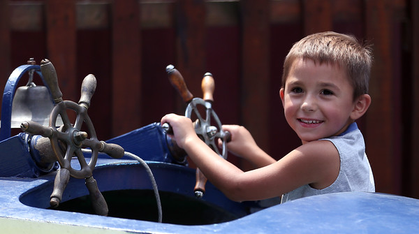 DAVID LE/Staff photo. Jack Clark, 4, of Ashby, smiles at his father while riding in a circle on a amusement ride in Salem Willows on Monday afternoon. 7/25/16.