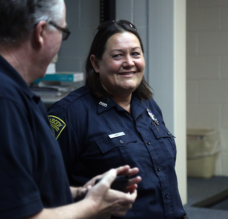 DAVID LE/Staff photo. Retiring Peabody Police officer Nancy Hart smiles as Peabody Police Chief Tom Griffin thanks her for her service to the Peabody Police Department, a career that spanned over 25 years. 7/22/16.