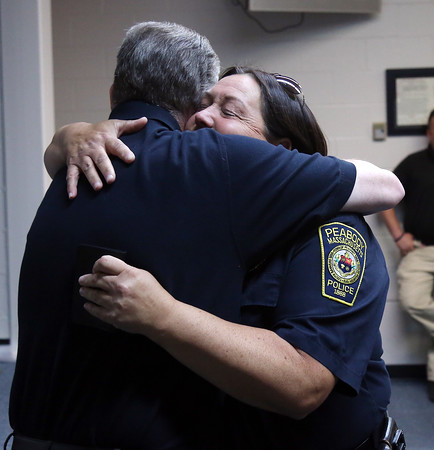 DAVID LE/Staff photo. Peabody Police Chief Tom Griffin gives retiring officer Nancy Hart a hug following a brief ceremony on Hart's last day, Friday afternoon. 7/22/16.