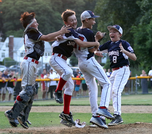 DAVID LE/Staff photo. Swampscott's Connor Correnti, and Nathan DeRoche, left, and Matt McIntire, right, mob closer Mathew Schroeder after he retired the last Peabody West batter to earn a save in the Big Blue's 10-7 win in the District 16 Championship. 7/15/16.