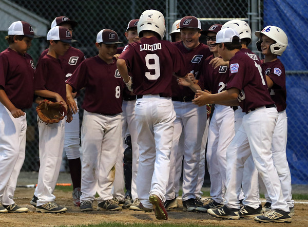 DAVID LE/Staff photo. The Gloucester District 15 little league team meets Jared Lucido at home plate following his homer against Manchester-Essex on Tuesday evening at Harry Ball Field. 7/12/16.