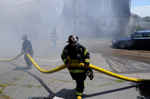 PAUL BILODEAU/Staff photo. Firefighters move a large hose as they battle a fast moving, multi-alarm fire on Bay View Drive in Swampscott.