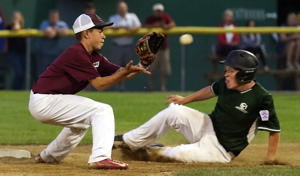 DAVID LE/Staff photo. Manchester-Essex's James McKenna, right, slides safely into second ahead of a tag from Gloucester shortstop Jared Lucido on Tuesday evening at Harry Ball Field. 7/12/16.