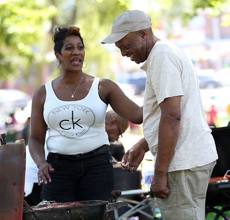 DAVID LE/Staff photo. Tonya Donald, of Dorchester, chats amicably with Arelein Pearson, of Boston, as they cook hot dogs on a small portable grill at the annual Black Picnic held at the Salem Willows on Saturday morning. 7/16/16.