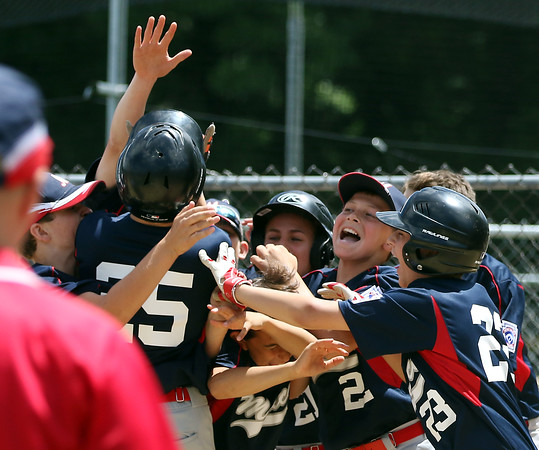 DAVID LE/Staff photo. The Masco little league team mobs teammate Kevin Pelletier after he crossed home plate after his walk-off two-run blast against Gloucester. 7/2/16.