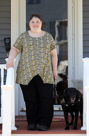 DAVID LE/Staff photo. Kayla Bentas, a 2009 graduate of Peabody Veterans Memorial High School, stands with her dog Haiku, a black labrador. Bentas is a member of the new Peabody Disabilities Commission, an idea that she pitched to Mayor Ted Bettencour. 7/12/16.
