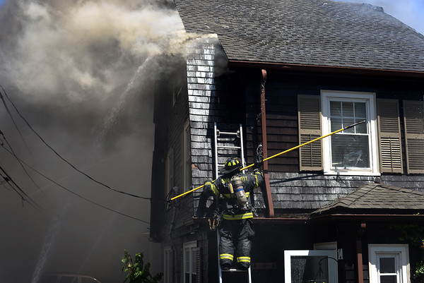 PAUL BILODEAU/Staff photo. A firefighter attempts to break a wind as firefighters battle a fast moving, multi-alarm fire on Bay View Drive in Swampscott.