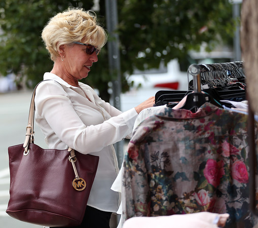 DAVID LE/Staff photo. Ellen Ferrante, of Beverly Farms, looks through a clothing rack outside Tess & Carlos, a storefront along Hale Street in Beverly Farms. Many local vendors set up tables and brought out goods for a sidewalk bazaar held all day Friday. 7/8/16.