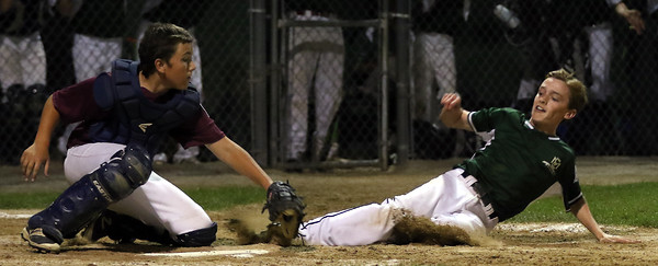 DAVID LE/Staff photo. Manchester-Essex's Peter Martin, right, slides into home and through the glove of Gloucester catcher Zach Oliver, knocking the ball loose to score another run on Tuesday evening at Harry Ball Field. 7/12/16.