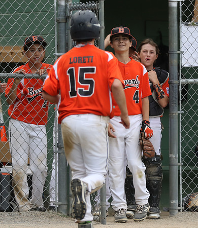 DAVID LE/Staff photo. Beverly's Dom Santos, left, Joe Brown (4), and Austin Bernard, right, wait to greet teammate Joe Loreti (15) after he scored the go-ahead run against Masco in District 15 play. 7/8/16.