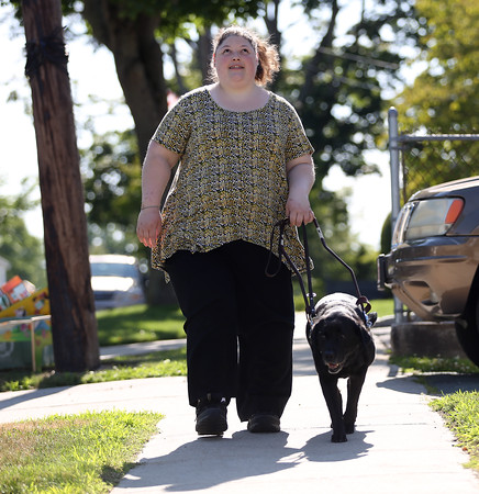 DAVID LE/Staff photo. Kayla Bentas, a 2009 graduate of Peabody Veterans Memorial High School, walks down her street with the aid of her sight dog Haiku, a black labrador. Bentas is a member of the new Peabody Disabilities Commission, an idea that she pitched to Mayor Ted Bettencour. 7/12/16.