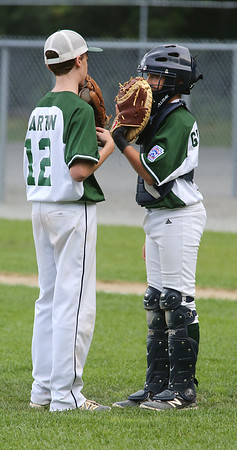 KEN YUSZKUS/Staff photo.    Manchester Essex's pitcher Peter Martin and catcher Charlie Gendron take a moment to talk tactics during the Boxford-Topsfield vs. Manchester Essex Little League playoff game at Harry Ball Field in Beverly.    07/11/16