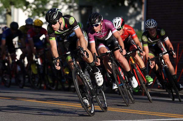 DAVID LE/Staff photo. Racers in the Men's Elite race of the Beverly Gran Prix whizz through a patch of sunlight while turning onto Cabot Street on Wednesday evening. 7/27/16.