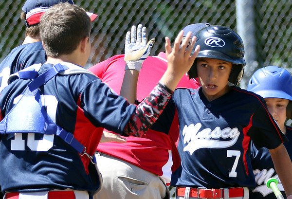 DAVID LE/Staff photo. Masco's Alec Aftandilan gets a high five from teammate Chris Milmoe (10) after crossing the plate against Gloucester. 7/2/16.