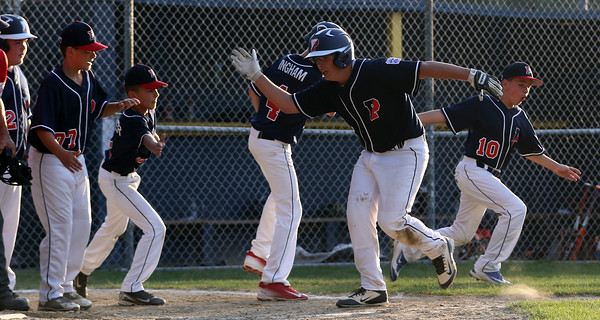 DAVID LE/Staff photo. Peabody West pitcher Dom Annese gets high fives from his teammates at home plate after he launched a homer against Swampscott. 7/15/16.