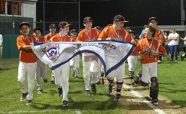 DAVID LE/Staff photo. Beverly players happily carry the District 15 banner around Harry Ball Field following their 4-2 win over Manchester-Essex on Thursday. 7/14/16.