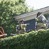 KEN YUSZKUS/Staff photo.  Firefighters work on the roof at the fire scene at the carriage house at Lynch Beach in Beverly.   07/04/16