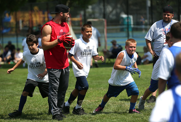 HADLEY GREEN/Staff photo<br /> Patriots wide receiver Julian Edelman scrimmages with players, from left, Jordan Grenier of Danvers, Kayden Tuck of Cape Cod, and Tommy Cyr of Danvers at the Julian Edelman Football Clinic at Danvers High School. 7/15/17