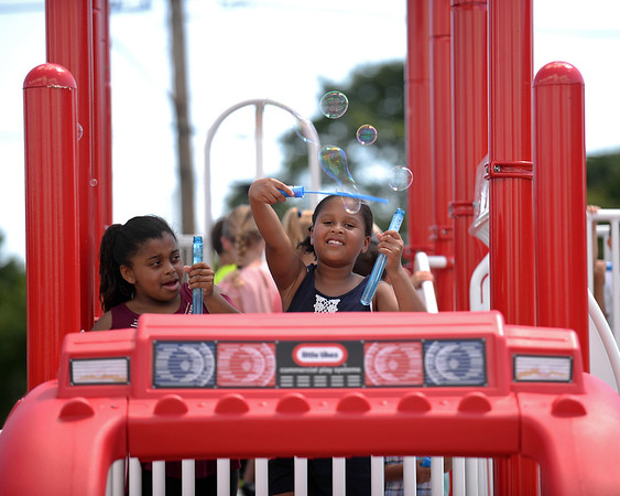 RYAN HUTTON/ Staff photo<br /> Amaya Hendricks, 8, right, waves a bubble wand as her friend Melissa Souza, 7, left, looks on during the opening of a new playground at South Memorial School in Peabody on Wednesday. The playground is named in honor of Ella Jade O'Donnell, a local 10-year-old who died of brain cancer last year.