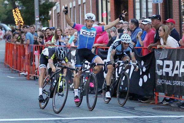 HADLEY GREEN/Staff photo<br /> Sam Rosenholtz celebrates before crossing the finish line, while Jacob Keough, to his left, speeds by him to finish first at the Men's State Championship race at the Grand Prix of Beverly. 7/26/17