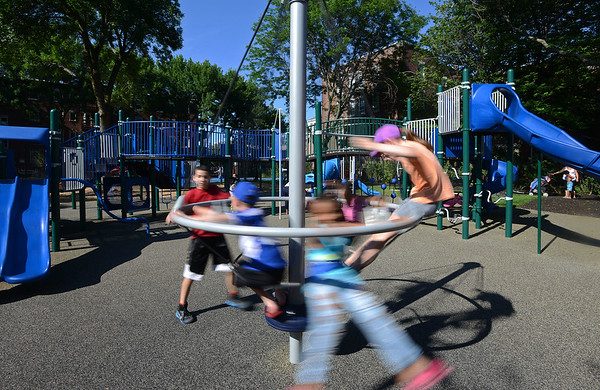 RYAN HUTTON/ Staff photo<br /> Children spin around on a new piece of playground equipment during the grand re-opening of the Mary Jane Lee Park in the Point in Salem on Wednesday.
