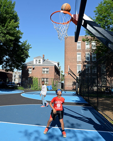 RYAN HUTTON/ Staff photo<br /> Christian Reyes, 14, shoots a layup as Utonneil Martin, 17, looks on during the grand re-opening of the Mary Jane Lee Park in the Point in Salem on Wednesday.