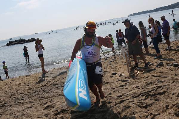HADLEY GREEN/ Staff photo<br /> Jeramie Vaine runs up the beach after coming in second at Paddle for Plummer's annual paddleboard race on Winter Island. 7/08/17