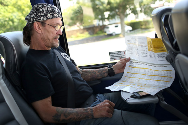 HADLEY GREEN/Staff photo<br /> Dana Dismore, who lives in Salem and works in Rockport, looks at the shuttle bus schedule while timing his ride on his phone. Dismore plans to take the Newburyport Rockport line shuttle bus to and from work during the service disruption. 7/18/17