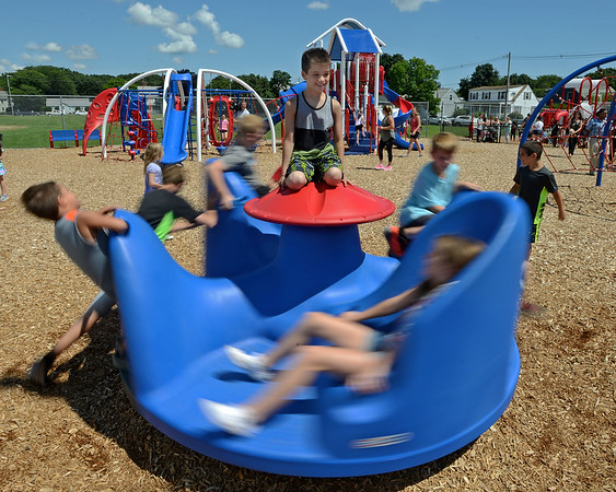 RYAN HUTTON/ Staff photo<br /> Casey Collins, 9, perches atop a merry-go-round during the opening of a new playground at South Memorial School in Peabody on Wednesday. The playground is named in honor of Ella Jade O'Donnell, a local 10-year-old who died of brain cancer last year.