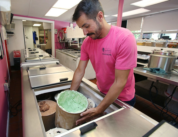 Ken Yuszkus/Staff photo       One of the owners, Michael Gould, moves a tub of pistachio ice cream at Treadwell's Ice Cream.        7/6/17