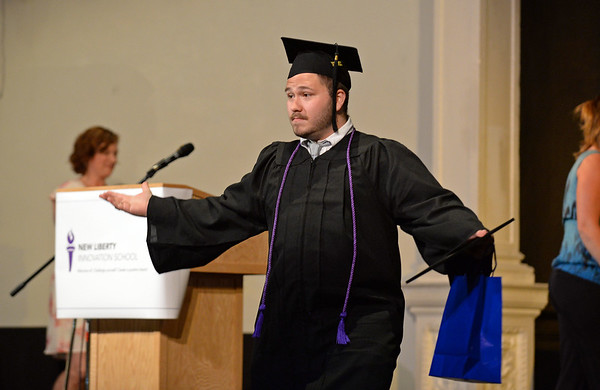 RYAN HUTTON/ Staff photo<br /> New Liberty Innovation School graduate Ryan Sullivan raises his arms to applause after receiving his diploma at the school's graduation ceremony at the Salem YMCA's Ames Hall on Thursday.