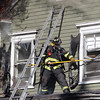 As the roof burns in the background, a Danvers firefighter takes out a second story window on Friday afternoon. A 3-alarm fire broke out at 8 Sylvan Street in Danvers on Friday afternoon. DAVID LE/Staff photo. 6/20/14