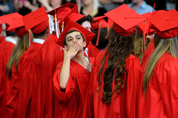 KEN YUSZKUS/Staff photo. Robbie Stokes throws kisses toward the audience as he arrived at his seat during the processional at the Salem High School graduation.  6/6/14.