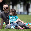 James Goncalves, of Salem and his daughter Maiah, 3, sit on the grass of Salem Common as performers from Pandion Entertainment perform a trapeze show at the annual Gay Pride Parade festivities at Salem Common on Saturday afternoon. DAVID LE/Staff photo. 6/21/14.