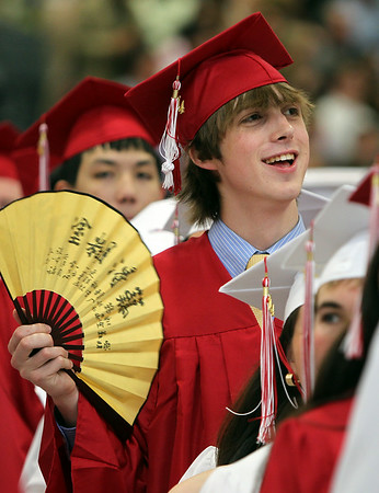 Masco graduate Matt Chadwick cools himself off with a fan while waiting for graduation to start on Friday evening. DAVID LE/Staff photo. 6/6/14.