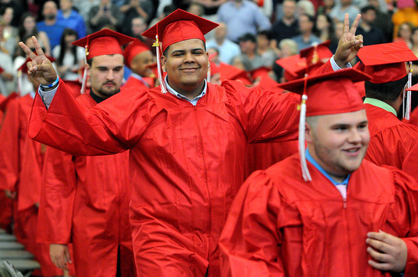 KEN YUSZKUS/Staff photo. Graduate Wilton Echavarria gives victory signs while walking to his chair during the processional at the Salem High School graduation.  6/6/14.