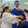 Danvers High School graduates Elizabeth Guay adjusts Daniel King's mortar board as Brett Owens looks on prior to the start of graduation on Saturday afternoon. DAVID LE/Staff photo. 6/7/14.