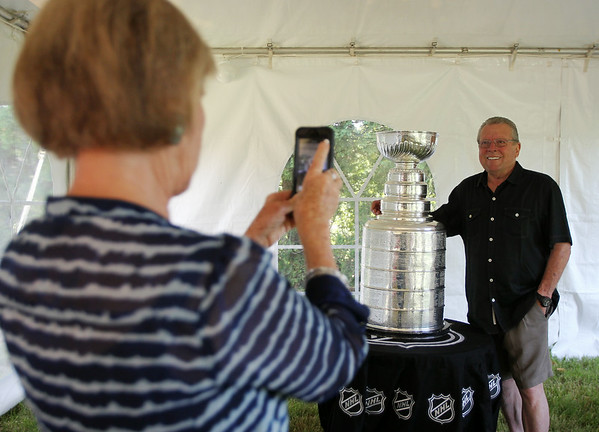 Wendy Hughes, of Newport Beach, CA, takes a photo of her husband Fred with the Stanley Cup on Sunday morning. Mark Yanetti, of Topsfield, the Director of Amateur Scouting for the Los Angeles Kings won the Cup for the second time in three years. DAVID LE/Staff photo. 6/29/14.