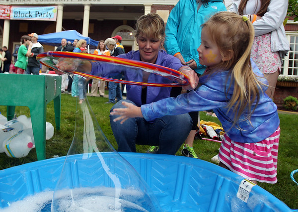 Three-year-old Abby Baker, of Wenham, plays with a large bubble made by her mom Regina Baker, during the 6th annual block party held at the Hamilton-Wenham Community House on Friday afternoon. DAVID LE/Staff photo. 4/13/14.