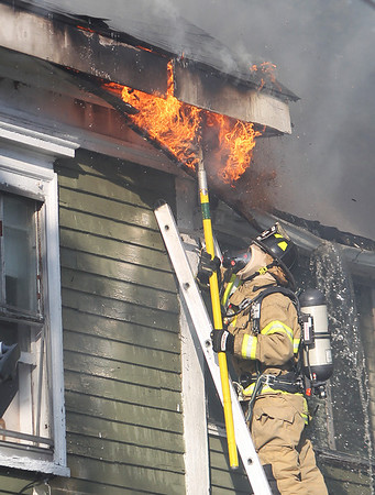 A firefighter uses a spear to break open a portion of the roof as flames spit through. A 3-alarm fire broke out at 8 Sylvan Street in Danvers on Friday afternoon. DAVID LE/Staff photo. 6/20/14